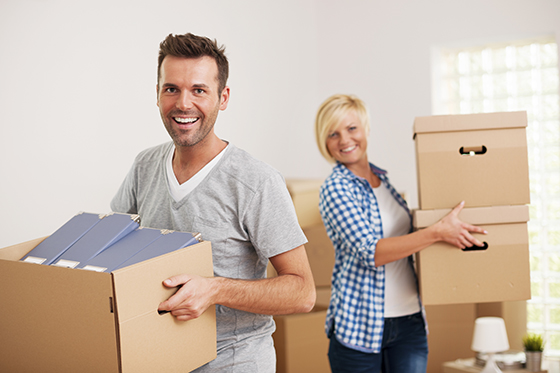 Portrait of happy couple carrying cardboard boxes in new home
