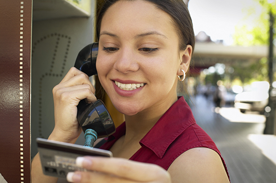 Woman on a pay phone holding credit card