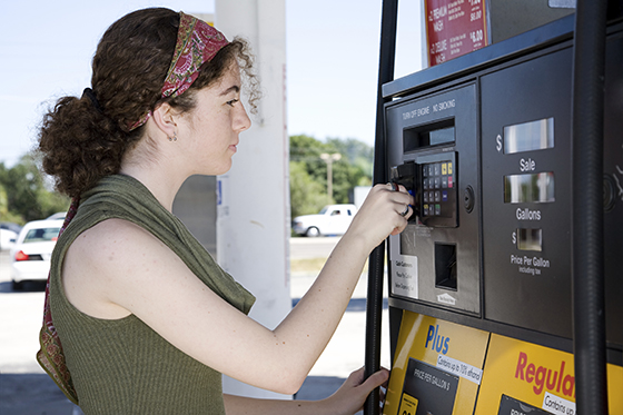 Woman buying gas at self serve pump