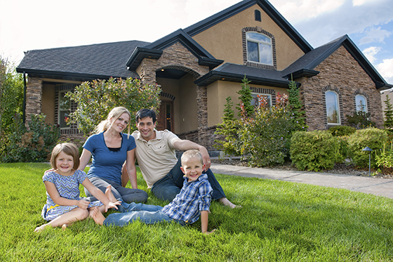 Family of Four on Lawn with Beautiful Home in Background
